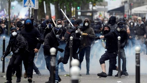 Demonstrators clash with police officers during a protest against proposed labour reforms in Paris, 14 June