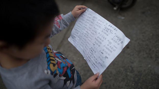 Niño mirando papel con sumas