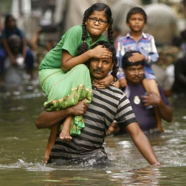 People carry children on their shoulders and wade through flood waters in Chennai, India, Thursday, Dec. 3, 2015.