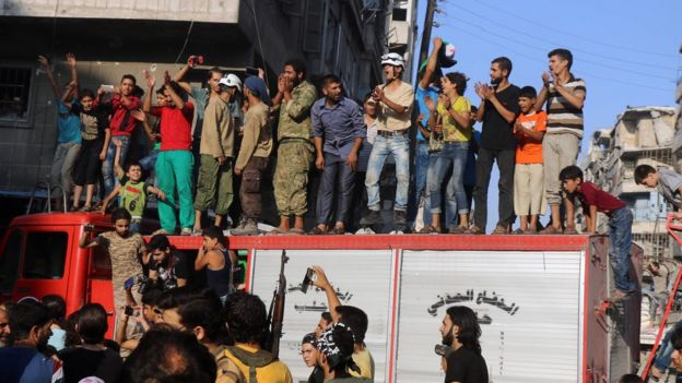 A group of men and boys gather on a vehicle in celebration