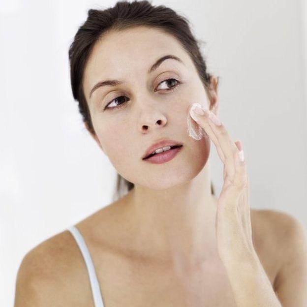 Mulher aplicando creme no rosto