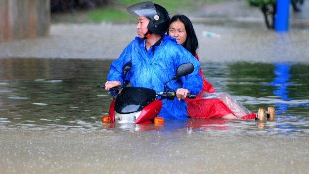 Jiangxi residents on a scooter in floodwater