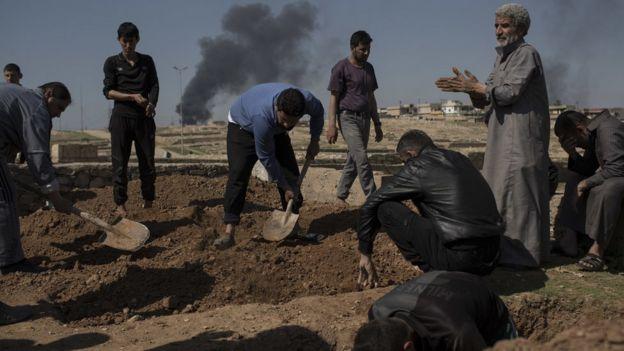 Homens preparam covas para enterrar vítimas de Mosul