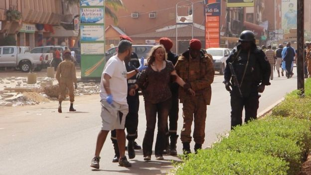 A woman being led to safety in Ouagadougou, Burkina Faso, Saturday Jan. 16, 2016