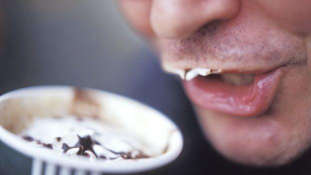 Homem tomando bebida à base de café com chantilly