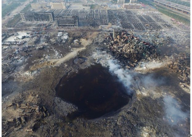 An aerial view on 15 August, 2015, of a large hole in the ground in the aftermath of a huge explosion that rocked the port city of Tianjin, China