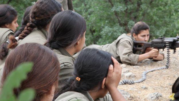 PKK fighters watch Amrin, a Yazidi, fire a machine-gun at a camp in northern Iraq