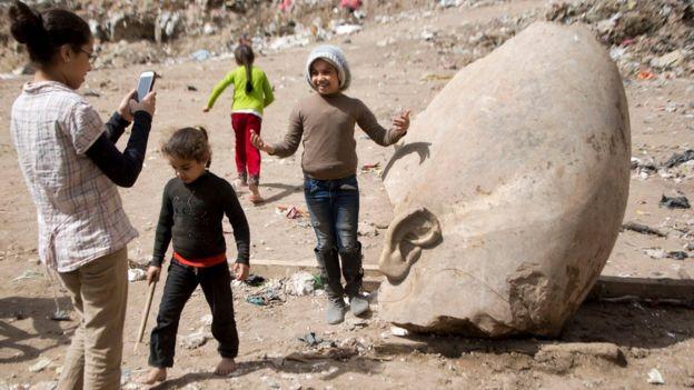 Una niña se retrata junto a uno de los restos de la estatua que pudo haber pertenecido al faraón Ramsés II.