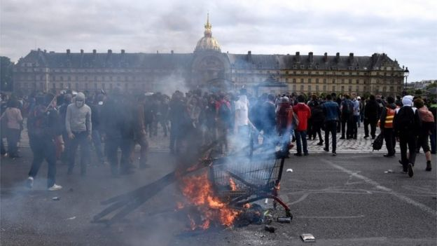 A shopping cart burns as protesters gather near the Invalides during a demonstration against proposed labour reforms in Paris on June 14, 2016.