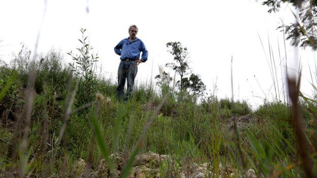 Hombre mira desde el borde de una fosa común.