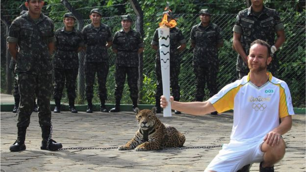 Brazilian physiotherapist Igor Simoes Andrade poses for picture next to jaguar Juma as he takes part in the Olympic Flame torch relay in Manaus, Brazil, 20 June 2016.