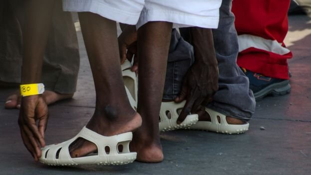 Migrants arriving in Palermo are provided with sandals