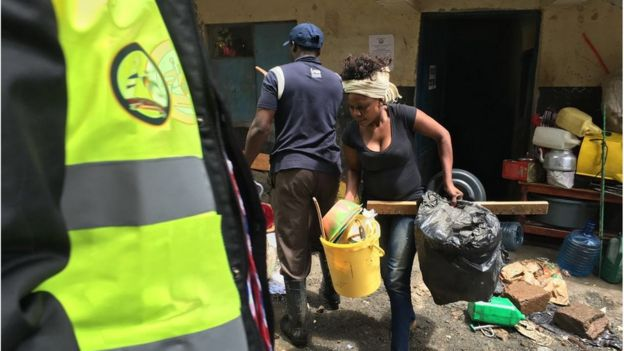 Woman taken her belongings out of her home in Hurama, Nairobi, 6 May 2016