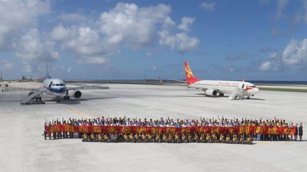 En enero de 2016, un grupo de gente posa con un banner delante de dos aviones chinos de pasajeros en el campo aéreo de Fiery Cross Reef, conocido como Yongshu Reef en chino.