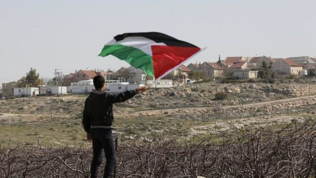 A Palestinian holds the Palestinian flag during a protest in the West Bank village of Twani, near Hebron, 10 February 2017.