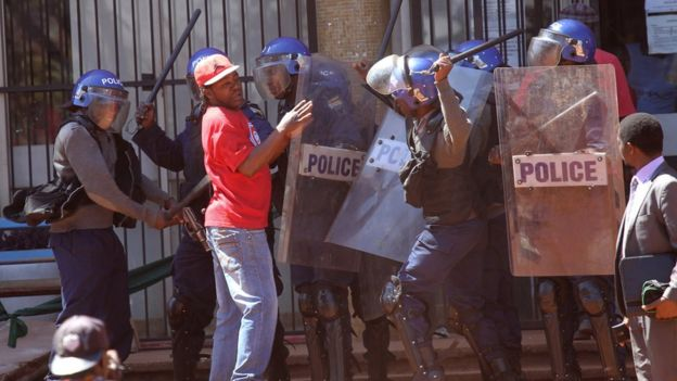 Police with batons clash with protester in red t shirt