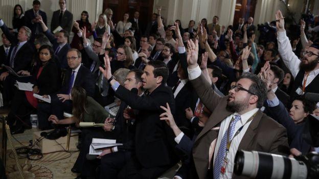 Periodistas levantando la mano.