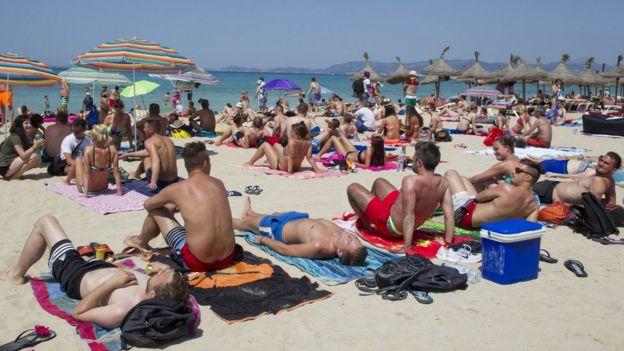 Turistas en una playa española.