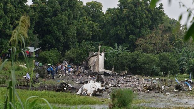 People gather at the site where a cargo plane crashed into a small farming community on a small island in the White Nile river