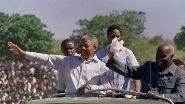 3 March 199: South African anti-apartheid leader and African National Congress (ANC) member Nelson Mandela (L) and Zambian President Kenneth Kaunda (R) wave to the crowd as they arrive at a mass rally in Lusaka