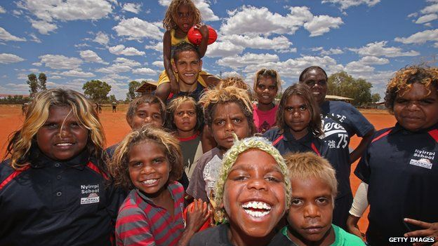 Dom Barry of the Indigenous All Stars poses with locals as members of the Indigenous All Stars visit Yuendumu School in the Australian outback , 2013