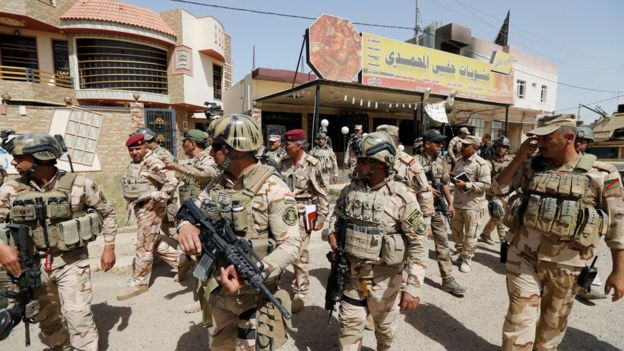 Iraqi soldiers walk through central Falluja (17 June 2016)