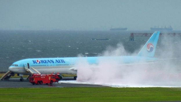 Smokes and foam sprayed by fire crews at Haneda airport, rises from a Korean Air plane on the tarmac on (27 May 2016)