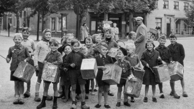 Niños con latas de galletas vacías en las calles de Amsterdam, alrededor de 1944.