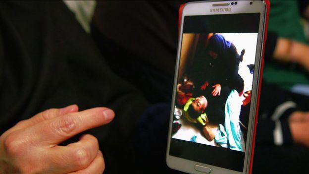 Petima, telefonundaki ölmüş eşinin fotoğrafını gösteriyor.