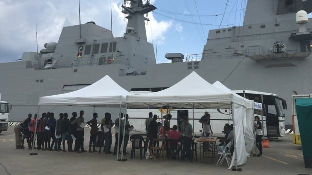 Asylum seekers from Libya queue after being brought to Messina on a rescue ship