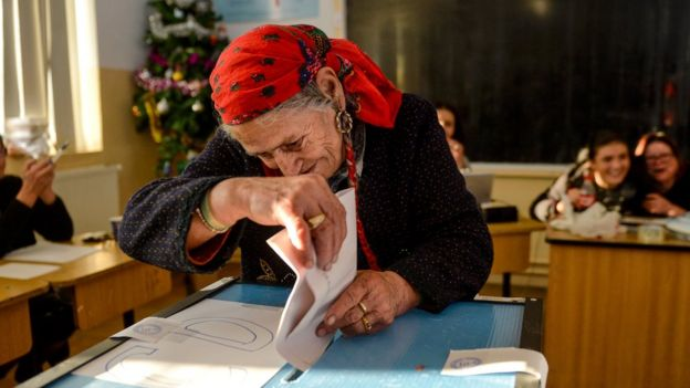 A woman wearing a red head scarf casts her vote in Sintesti, south of Bucharest, Romania