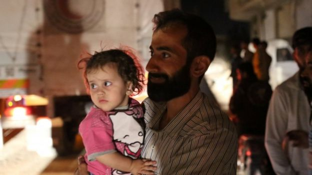 A man holds a child as supplies arrive in Daraya