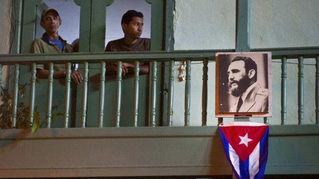 Dos residentes de La Habana con un retrato de Fidel Castro