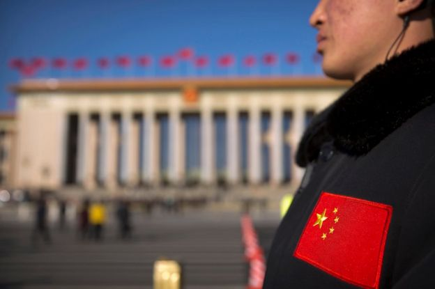 In this 12 March 2017 photo, a security official with a Chinese flag patch on his jacket stands guard outside of the Great Hall of the People before a plenary session of the National People's Congress (NPC) in Beijing, China.