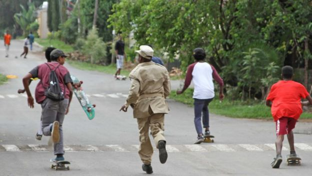 three boys skateboard away with a security guard in pursuit