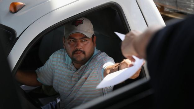 A Mexican trucker hands over manifest documents to a U.S. Customs and Border Protection officer in Laredo, Texas (17 October 2016)