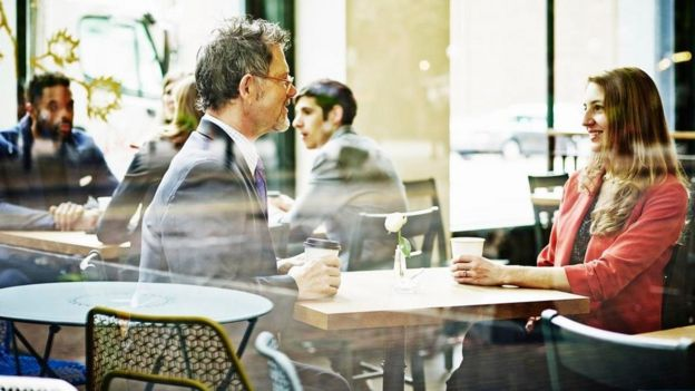 Un hombre y una mujer conversan en un café