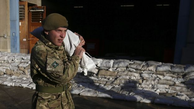 A soldier carrying a sandbag