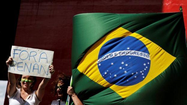 Protesta en Sao Paulo con una bandera brasileña y un cartel que dice