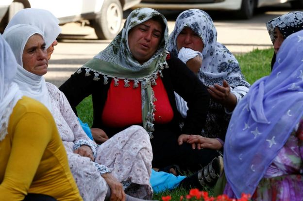 Women wait outside a morgue in the Turkish city of Gaziantep, 21 August