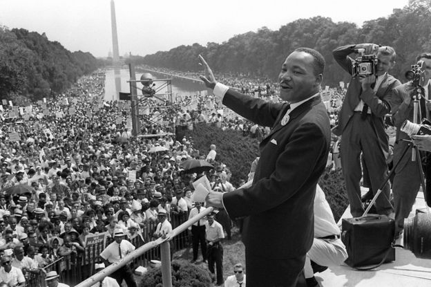 US civil rights leader Martin Luther King, Jr., waves to supporters from the steps of the Lincoln Memorial 28 August, 1963, on The Mall in Washington, DC