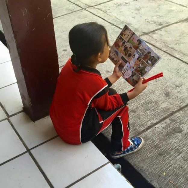 An Indonesian girl reading the comic book that warns of trafficking