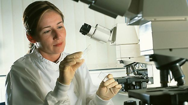 Female scientist studying a slide