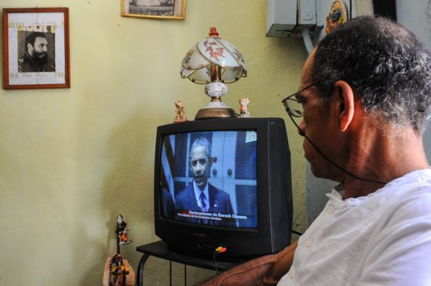 A man in Havana watches President Obama announce a restoration of diplomatic ties between Cuba and the US as a photo of Fidel Castro hangs on the wall, in July
