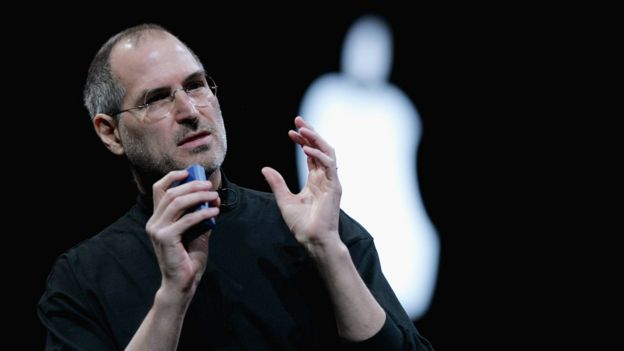 Steve Jobs gives a talk in front of an Apple logo