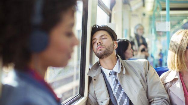 Hombre con los ojos cerrados en un medio de transporte.