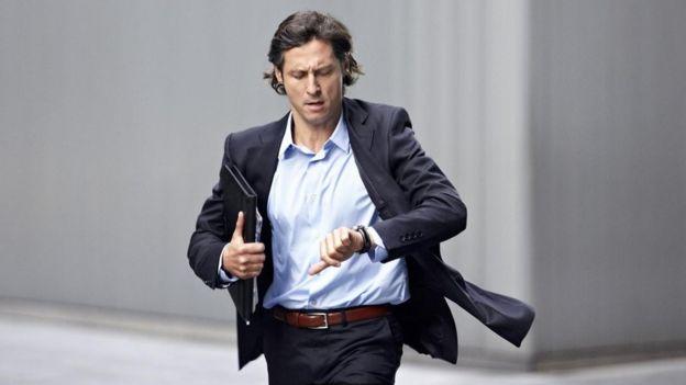Un hombre apurado, mirando su reloj