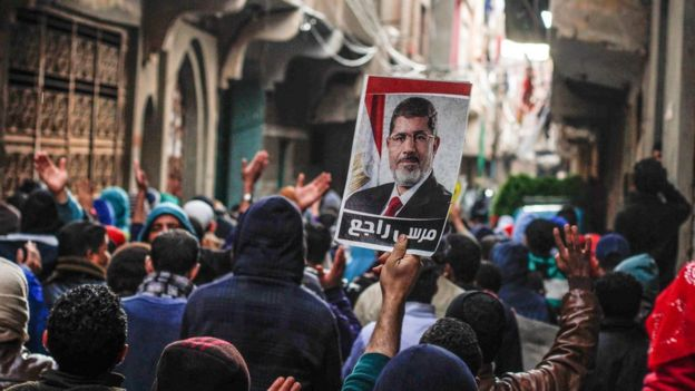 Morsi supporters hold up a photo of the ousted president on the fifth anniversary of the 2011 uprising in Cairo, Egypt (25 January 2016)