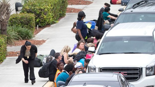 People take cover behind vehicles at Fort Lauderdale's International Airport