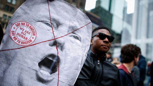 Un hombre negro sostiene una pancarta con la cara de Trump tachada con una equis